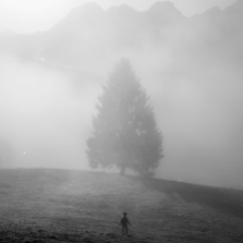 Family quarantining in the mountains during the Covid-19 pandemic. Emma, 6, runs through a field in front of the farmhouse we were staying in. Switzerland, 2020. ©Paolo Pellegrin/Magnum Photos